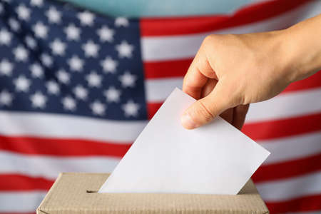 Man putting ballot into voting box against american flag 版權商用圖片