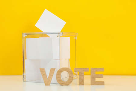 Voting box with bulletins and text Vote on yellow background, space for text
