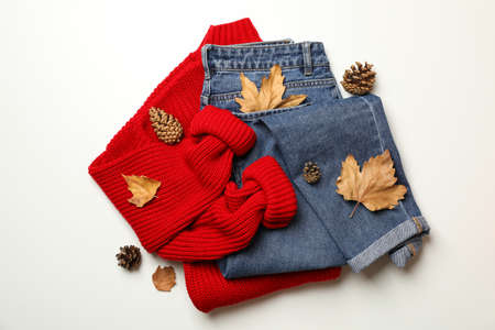 Sweater, jeans, cones and leaves on white background