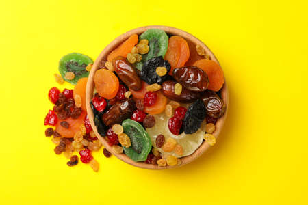 Wooden bowl with dried fruits on yellow background