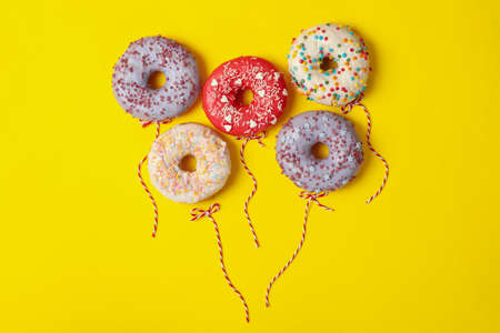 Concept of balloons made of donuts on yellow background