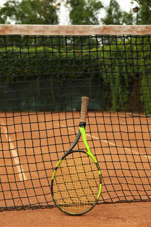 Net with tennis racket on clay court