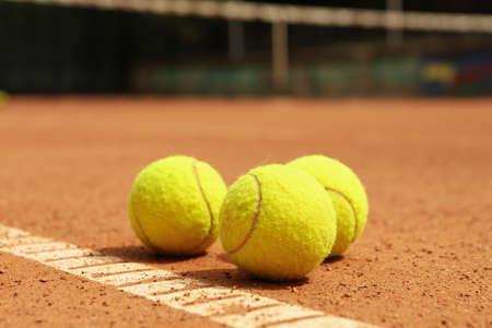 Light green tennis balls on clay court
