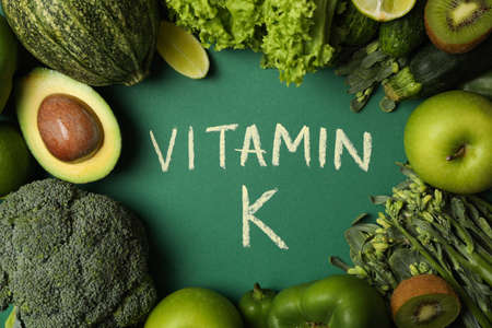 Vegetables, fruits and text Vitamin K on green background