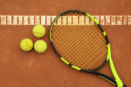 Tennis racquet with tennis balls on clay court
