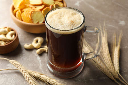 Beer, wheat and snacks on gray background, close up Imagens