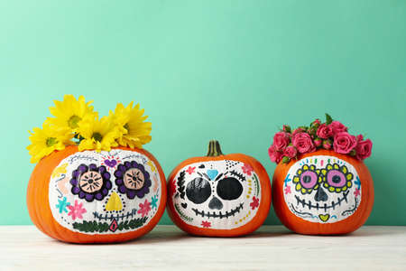 Pumpkins with catrina skull makeup and flowers on mint background