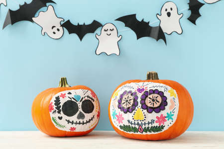 Pumpkins with catrina skull makeup, ghosts and bats on blue background