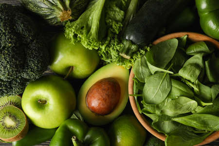Green vegetables and fruits on wooden background, top view Stock fotó
