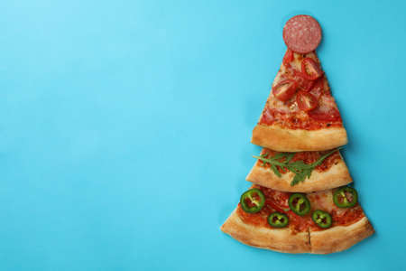 Christmas tree made of pizza slices on blue background