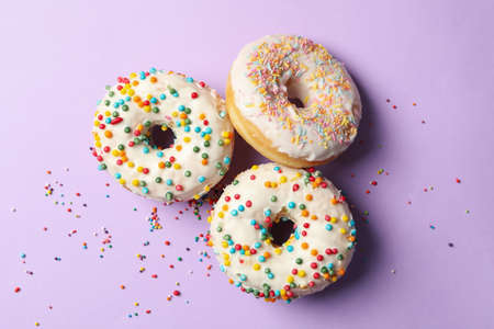 Three tasty donuts on violet background, top view Фото со стока