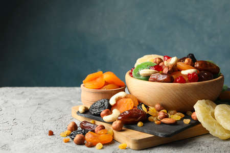Board and bowls with dried fruits and nuts on gray background