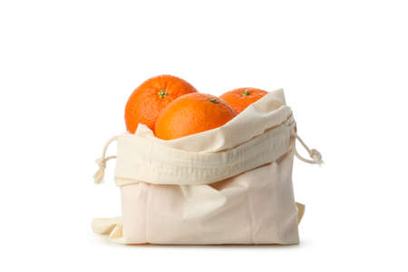 Cotton bag with ripe mandarins isolated on white background