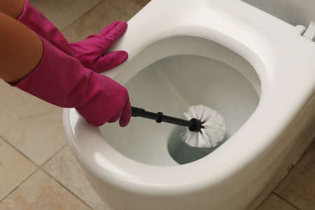 Woman in rubber pink gloves cleans toilet bowl with brush