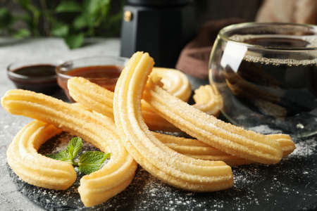 Concept of lunch with sweet churros on gray table
