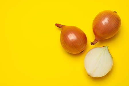 Fresh raw onion on yellow background, top view