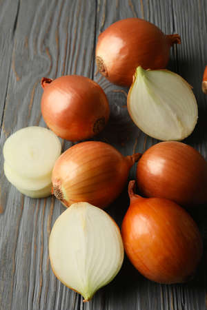 Fresh raw onion on wooden background, close up
