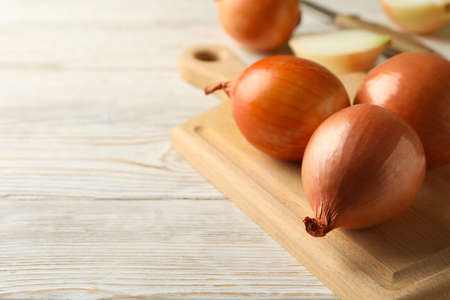 Board with onion and knife on wooden background