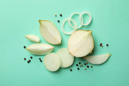 Fresh onion and peppercorns on mint background, top view