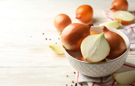 Bowl with fresh onion and napkin on wooden background Banco de Imagens