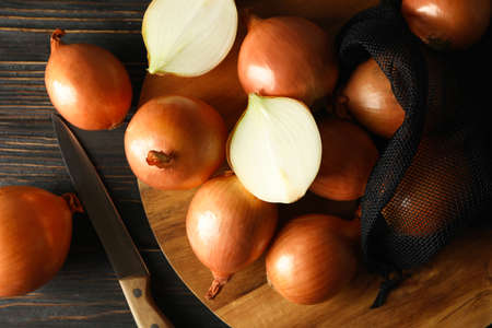 Board with fresh onion on wooden background Banco de Imagens