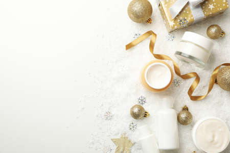 Concept of face care with cosmetics on background with decorative snow