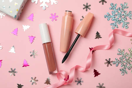 Cosmetics and Christmas accessories on pink background