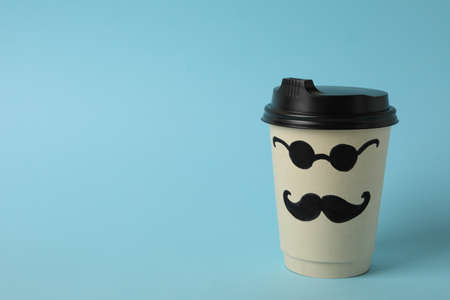 Paper cup with painted mustaches and glasses on blue background