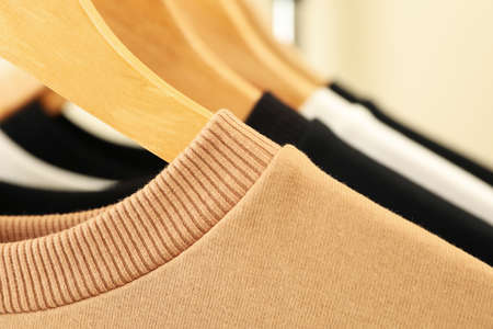 Hangers with stylish sweatshirts, close up and space for text