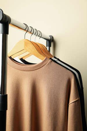 Hangers with stylish sweatshirts on beige background