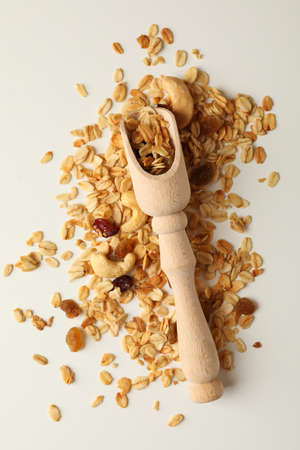 Wooden scoop and granola on white background