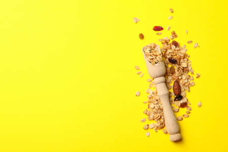 Wooden scoop and granola on yellow background