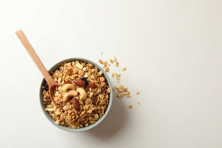 Bowl and spoon with tasty granola on white background