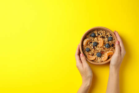 Female hands hold bowl with granola on yellow background, top view 免版税图像