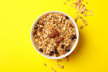 Bowl with granola with nuts and raisins on yellow background 免版税图像