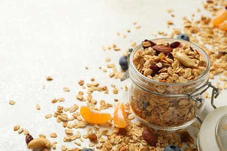 Glass jar with tasty granola on white background 免版税图像