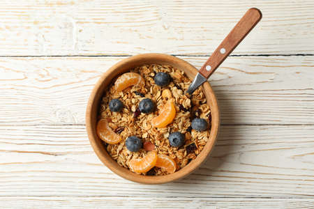 Bowl with granola and spoon on wooden background