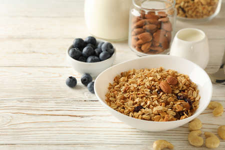 Concept of tasty breakfast with granola on wooden background