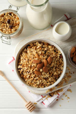 Concept of tasty breakfast with granola on white wooden background