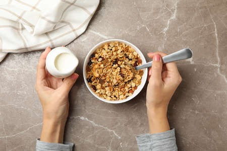 Woman eats granola on gray background, top view