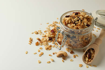 Glass jar and scoop with granola on white background