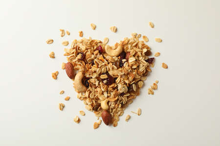 Heart made of granola on white background, top view 免版税图像