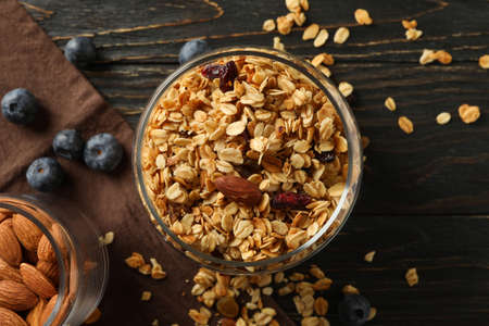 Glass jar with tasty granola on wooden background