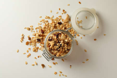 Glass jar with granola on white background