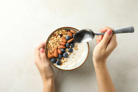 Woman eats granola on white background, top view