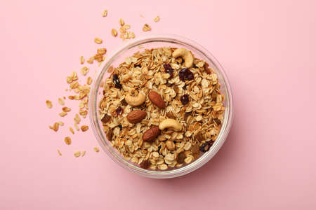 Bowl with tasty granola on pink background