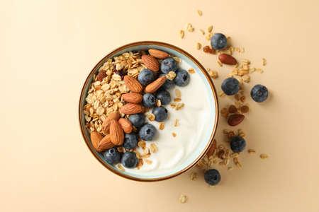 Bowl with tasty granola on beige background