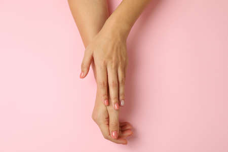 Cute female hands on pink background, top view 免版税图像