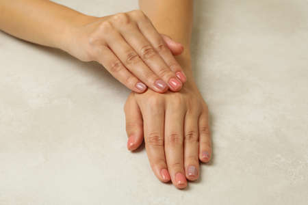 Female hands with pink nails on white background 免版税图像