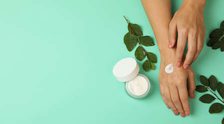Female hands with cosmetics cream on mint background